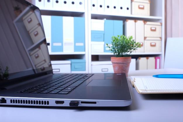 Büroarbeitsplatz mit laptop und intelligentem telefon auf hölzerner tabelle