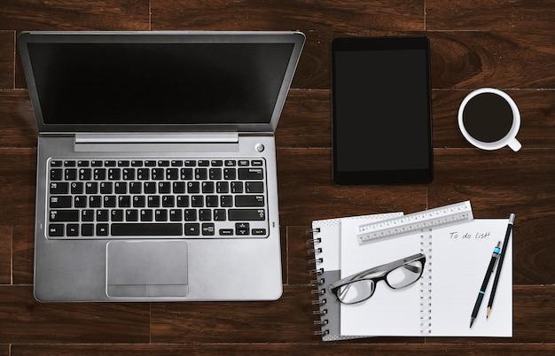 Büroarbeitsplatz mit laptop und notizbuch mit brillen und tablette. draufsicht.