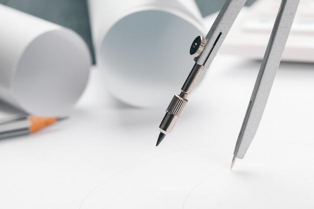 Büroarbeitsplatz mit leerem papier, bleistiften und verschiedenen ziehwerkzeugen, draufsicht
