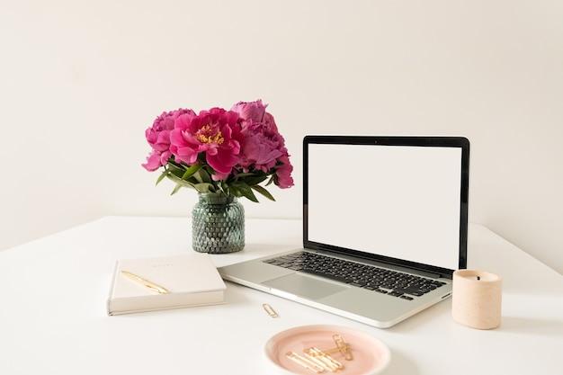 Büroarbeitsplatz tischarbeitsplatz mit leerem kopierraum modell laptop-bildschirm. modernes stilvolles hauptinnendesign mit blumenstrauß der rosa pfingstrosen.