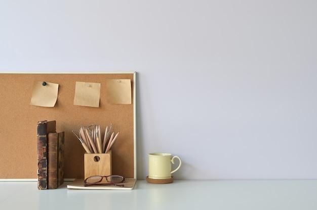 Büroarbeitsplatzkaffee, -bleistift, -bücher und -notizbuch an bord mit kopienraum.