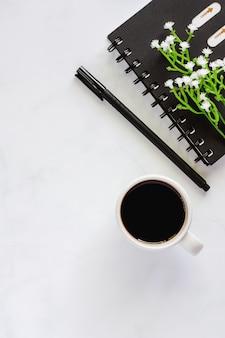 Büroartikel mit gewundenem notizbuch, stift, tasse schwarzem kaffee und kleiner künstlicher anlage