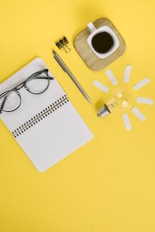 Büroartikel mit stift, notizblock, brille, tasse kaffee und glühbirne