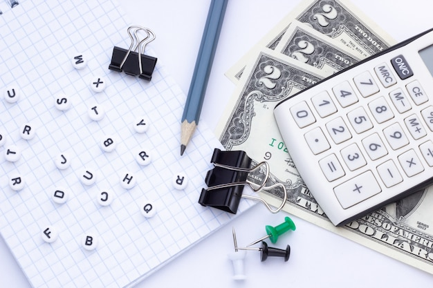Büroartikel, notizblock und geld auf einem weißen hintergrund