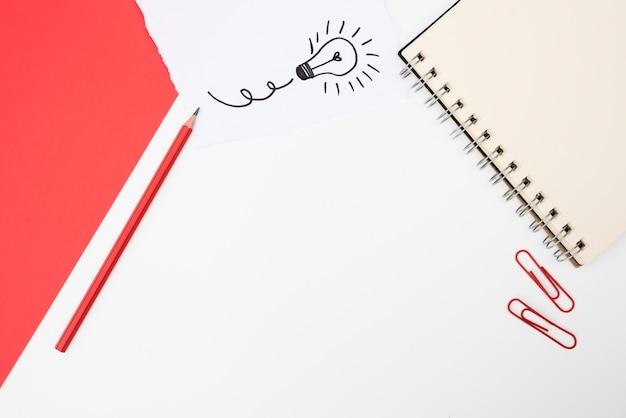 Büroartikel und weißes kartenpapier mit hand gezeichneter glühlampe über weißer oberfläche