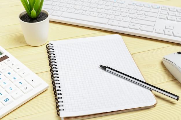 Büroausstattung wie computertastatur und andere versorgungen auf holztisch