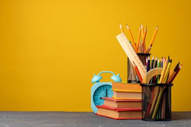 Bürobecher mit stiften und briefpapier gegen gelbe hintergrundvorderansicht
