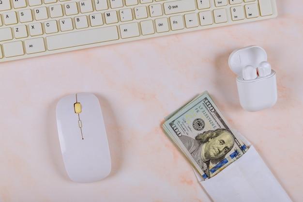 Bürobedarf, gadgets mit kabelloser ladetasche, kopfhörertastatur und maus, bargeld von einhundert dollar haufen