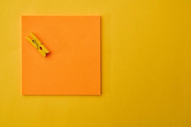 Bürobedarf, notizblock und clip auf gelbem hintergrund. schul- oder bildungszubehör, schreib- und zeichenwerkzeuge