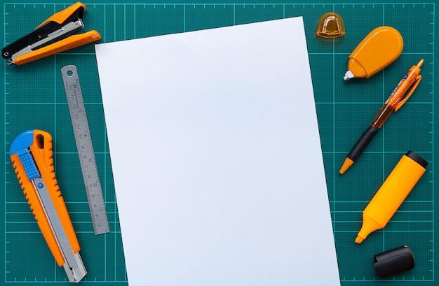 Bürobedarf und papier auf schneidematte, flaches lagebild.