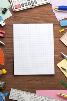 Bürobedarf und überprüftes notizbuch auf holzhintergrund