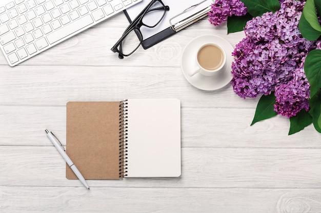 Bürodesktop mit einem blumenstrauß von fliedern, von kaffeetasse, von tastatur, von notizbuch und von stift auf weißen brettern