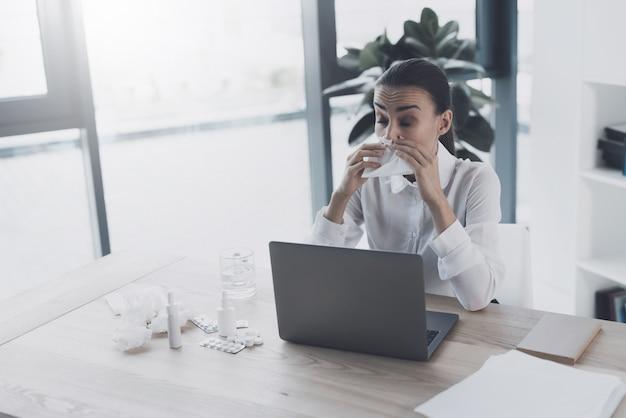 Bürofrau sitzt an ihrem arbeitsplatz und nimmt pillen