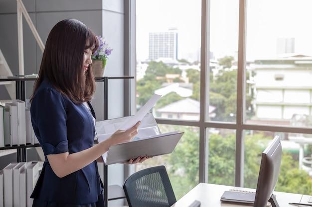 Bürofrau steht und beobachtet die dokumentendatei