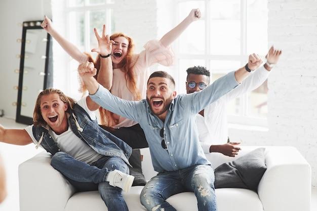Bürofreunde haben eine fröhliche zeit, die auf dem weißen sofa sitzt und liegt