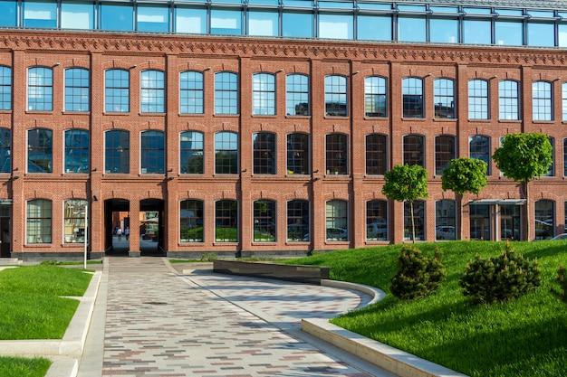 Bürogebäude aus rotem backstein im hof einer alten fabrik. mehrere bäume und eine wiese.
