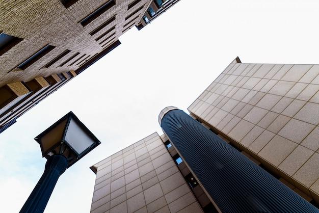 Bürogebäude vor wohnhäusern, durch einen laternenpfahl getrennt.