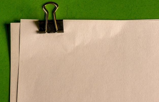 Büroklammer, weißbücher für notiz auf grünbuchhintergrund.
