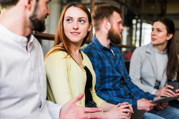 Bürokollegen, die miteinander am arbeitsplatz sich besprechen