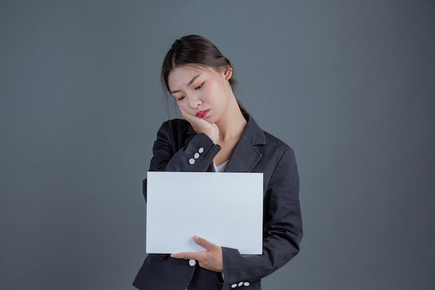 Büromädchen, das ein weißes leeres brett hält
