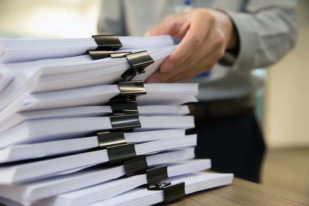 Büromänner wählen dokumente auf dem tisch aus.