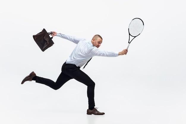 Büromann spielt tennis auf weiß