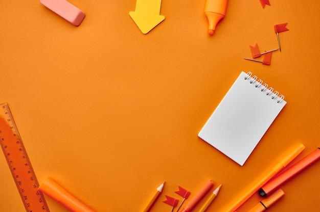 Büromaterial liefert, makroansicht, orange hintergrund. schul- oder bildungszubehör