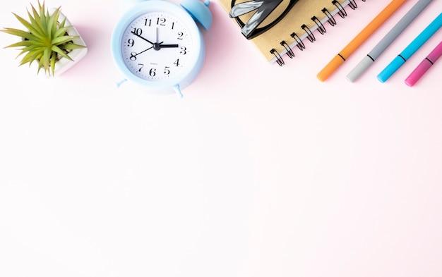 Büromaterial liegt auf einem rosa hintergrund. in der schule lernen. regenbogenfarbe.