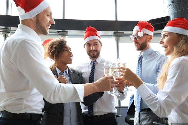 Büromitarbeiter feiern gemeinsam winterferien bei der arbeit und trinken champagner im büro. frohe weihnachten und ein glückliches neues jahr.