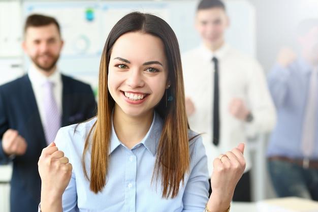 Büroporträt der lächelnden schönheitsgeschäftsfrau, das auf hintergrund des gruppengeschäftsvolkes steht. demonstriert die freude am ende des berichtszeitraums und das energiekonzept