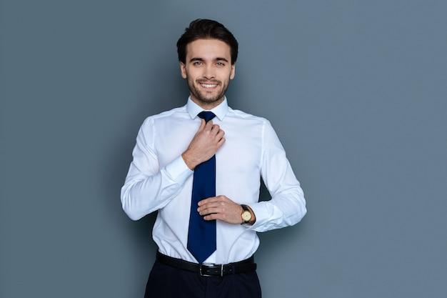 Bürostil. hübscher entzückter positiver mann, der sie ansieht und seine krawatte repariert, während er sich bereit macht, zu arbeiten