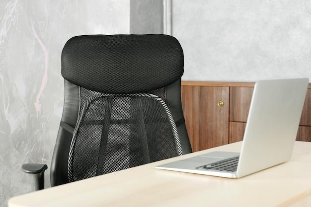 Bürostuhl mit netz zur rückenstütze und laptop auf dem tisch