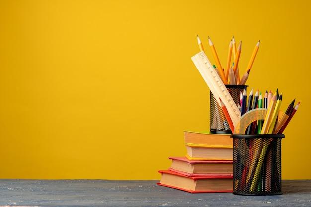 Bürotasse mit stiften und briefpapier gegen gelb