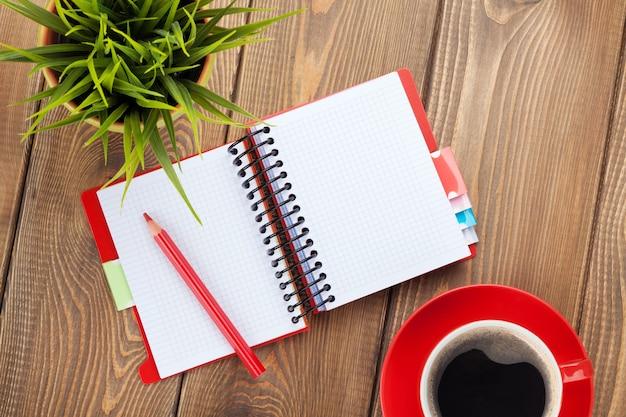 Bürotisch mit blume, leerem notizblock und kaffeetasse. ansicht von oben mit kopienraum