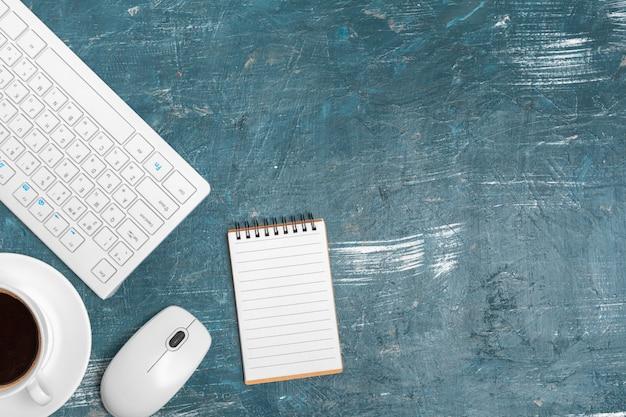 Bürotisch mit briefpapier, computertastatur und versorgungen nah oben