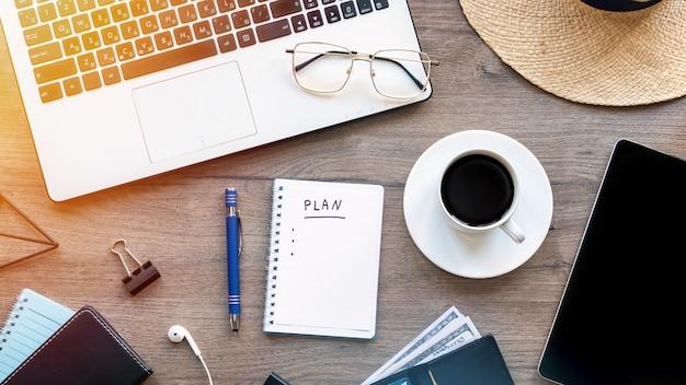 Bürotisch mit einem notizbuch und einem laptop auf hölzernem hintergrund