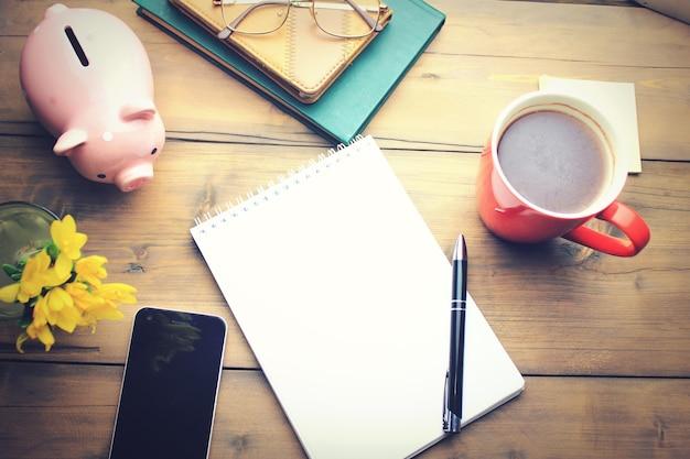 Bürotisch mit kaffeetasse, plan auf notizblock