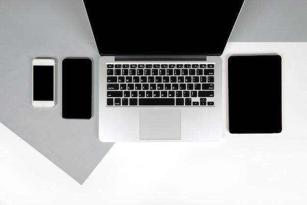 Bürotisch mit laptop-computer, notizbuch, digitaler tablette und handy auf zwei ton b