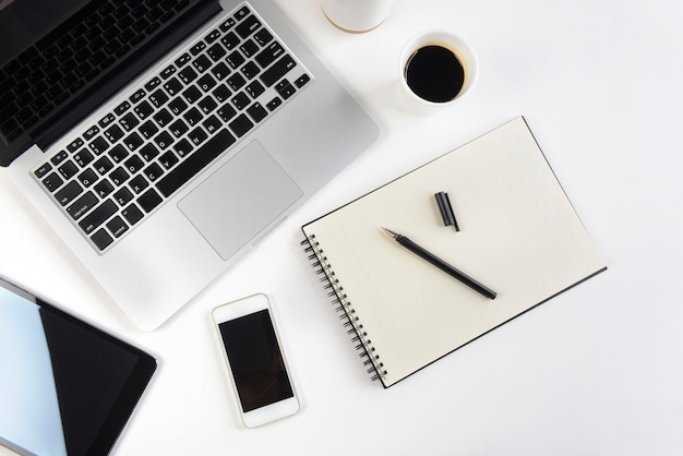Bürotisch mit laptop-computer, notizbuch, digitaler tablette und smartphone auf weißem hintergrund.