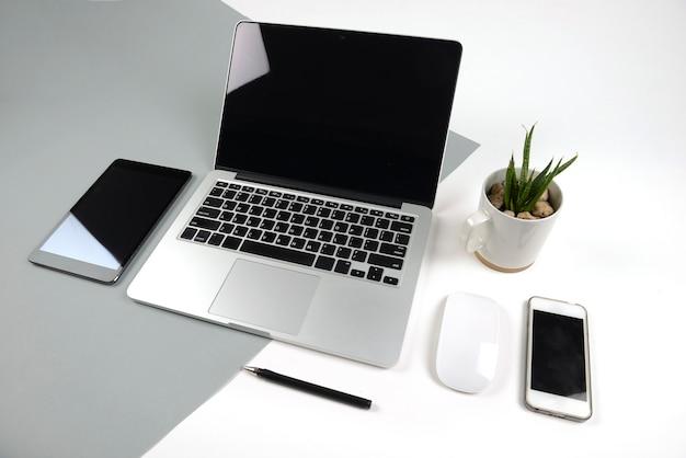 Bürotisch mit laptop-computer, notizbuch, digitaler tablette und smartphone auf zwei ton-ba