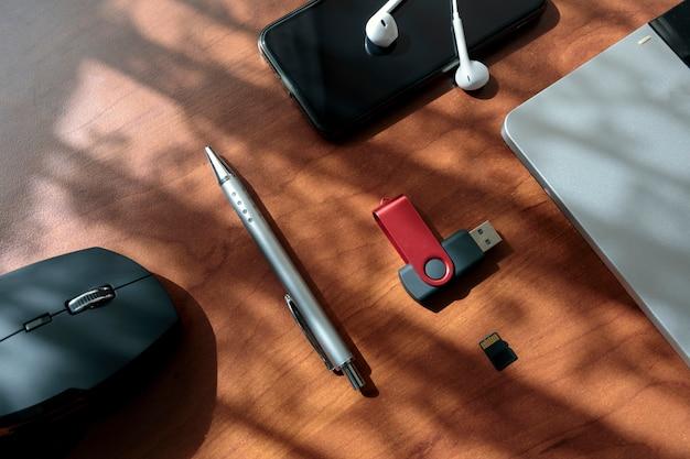 Bürotisch mit laptop, maus, smartphone, usb. büroarbeitsschreibtischwerkzeuge zeigen weinleseton mit kopienraum an.