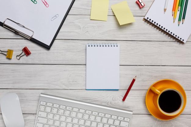 Bürotisch mit laptop, notizblock und kaffeetasse. ansicht von oben mit kopienraum