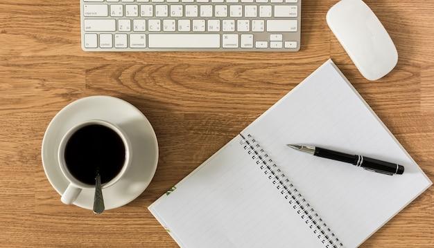 Bürotisch mit notizblock, computer und kaffeetasse und computermaus und stift
