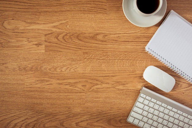 Bürotisch mit notizblock, computer und kaffeetasse und computermaus
