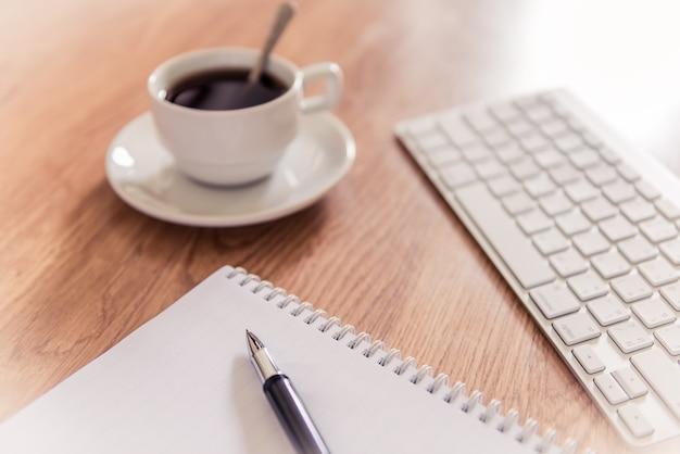 Bürotisch mit notizblock, computertastatur und kaffeetasse und stift