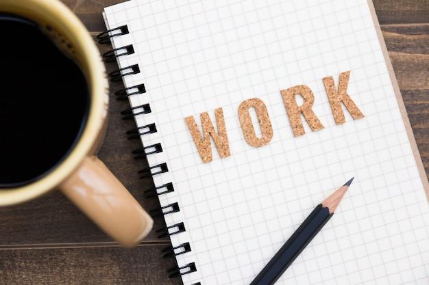 Bürotisch mit notizbuch, bleistift und kaffeetasse. von oben betrachten. arbeitskonzept.