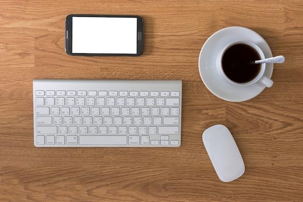 Bürotisch mit tastaturcomputer und kaffeetasse und computer-maus und smartphone