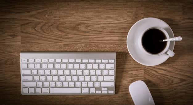 Bürotisch mit tastaturcomputer und kaffeetasse und computer-maus