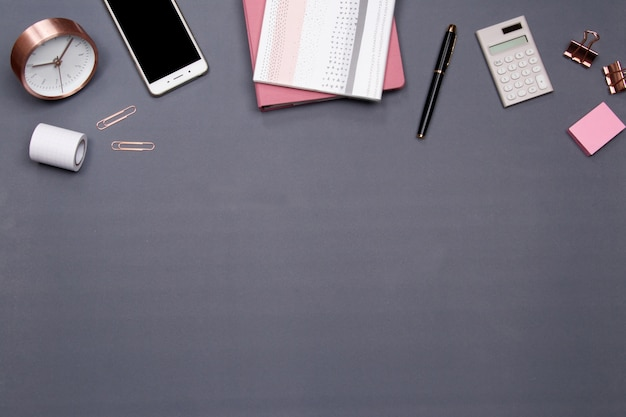Bürotisch schreibtisch mit smartphone und anderen büromaterial auf grauem hintergrund.