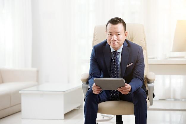 Bürovorsteher, der in seinem stuhl mit der digitalen auflage betrachtet kamera sich entspannt